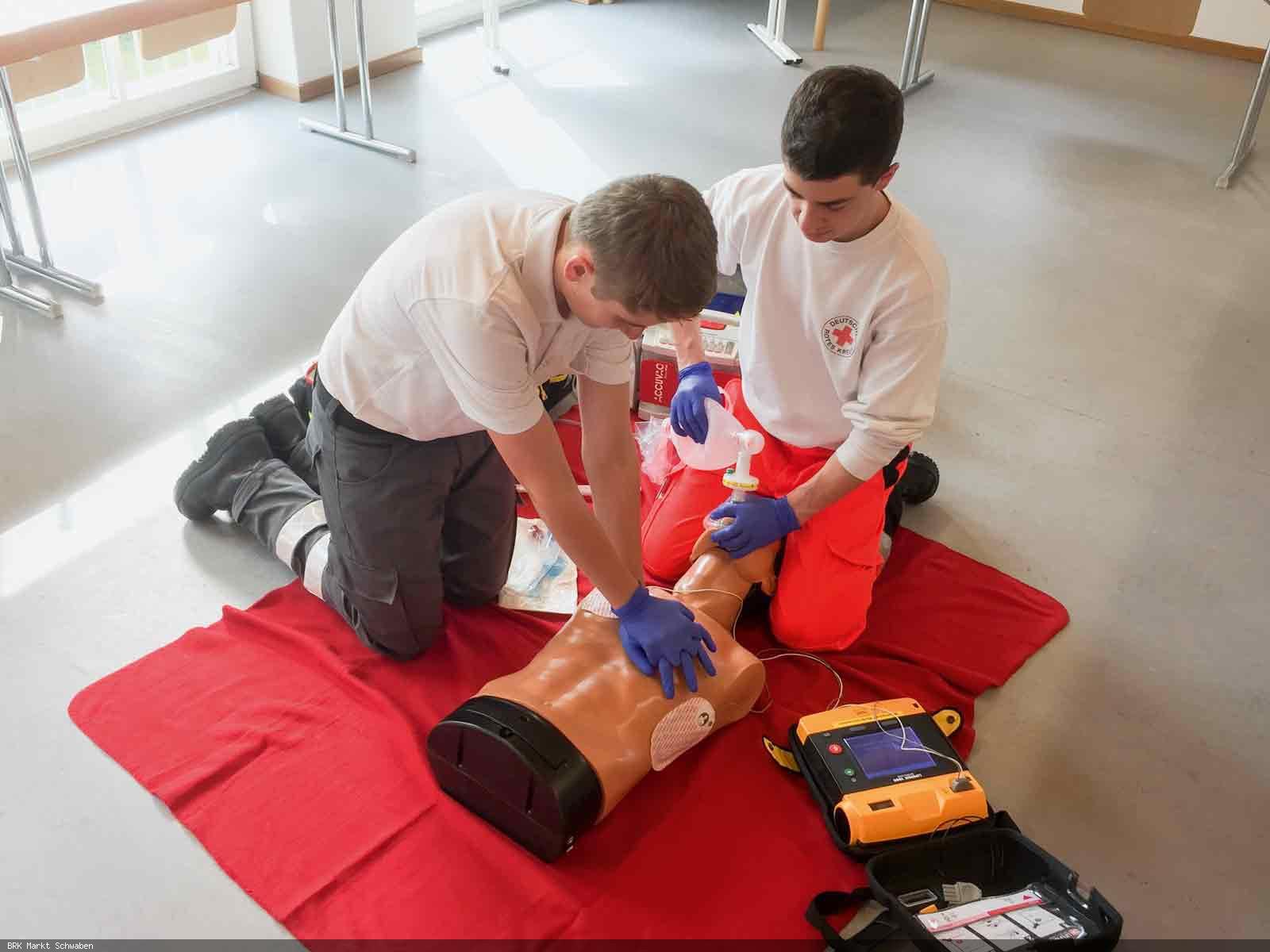 Rettungssanitäter führen den Defibrillator vor